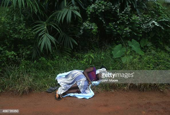 A woman lies alongside the road while waiting to enter the Ebola treatment center at the Island Hospital on October 6 2014 on the outskirts of...