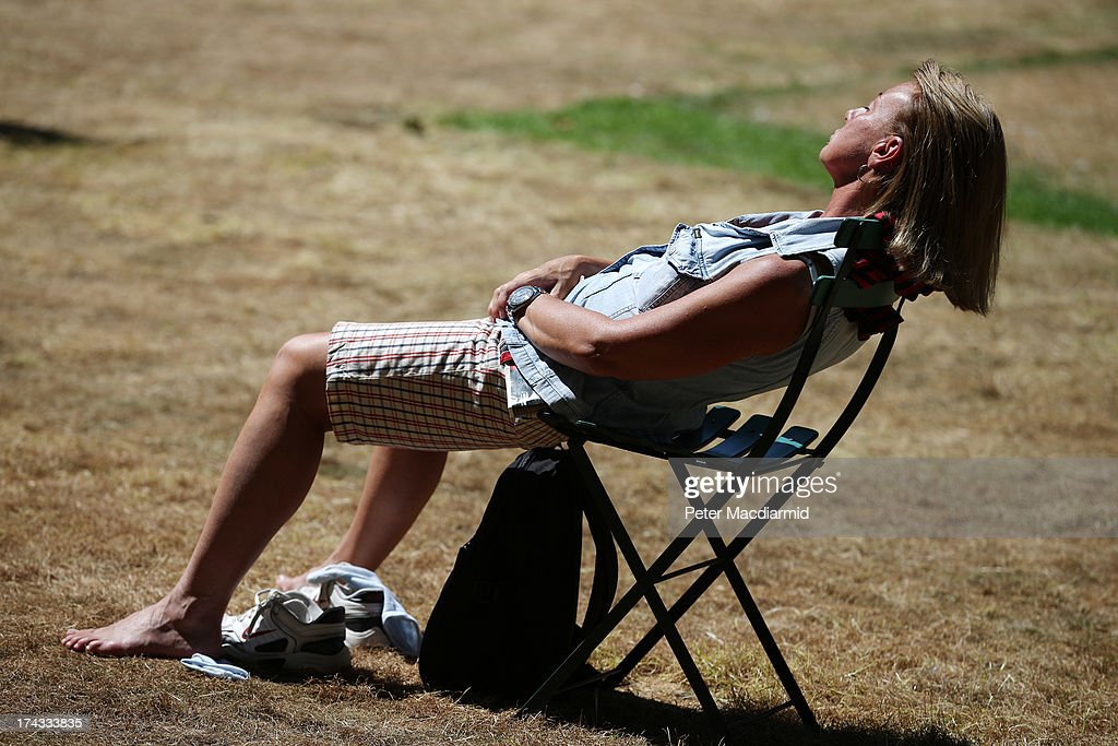 A woman lies back on a chair as she listens to the Cobham Brass Band playing in College Garden in the grounds of Westminster Abbey on July 24, 2013 in London, England. A series of lunchtime concerts entitled 'Brass on the Grass' are being held between July 24 and August 28, 2013.