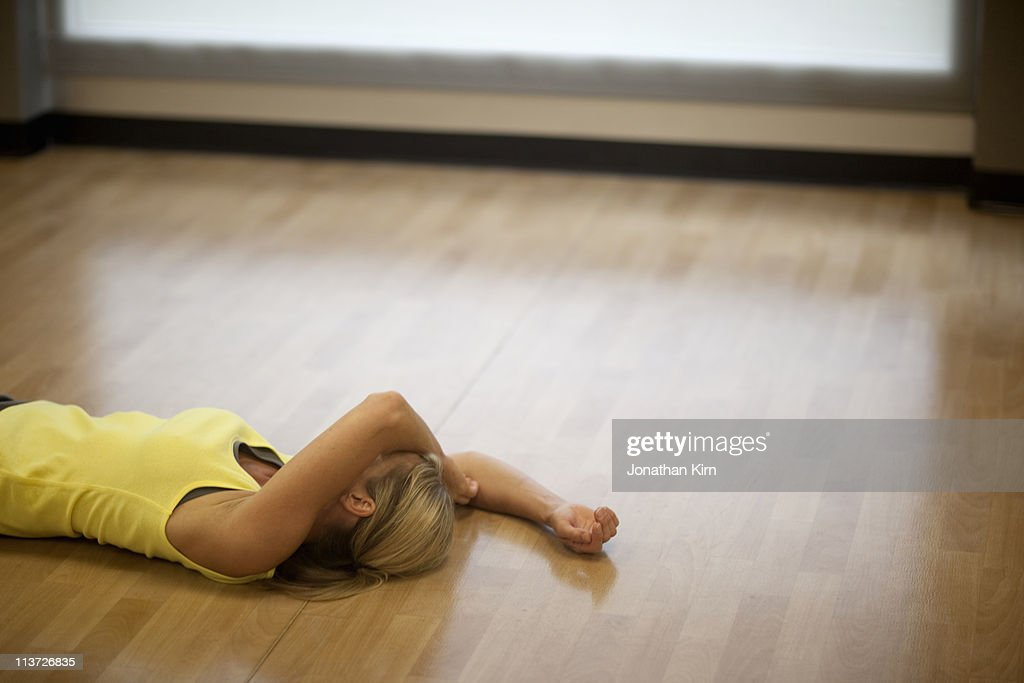 Woman lies exhausted on the gym floor. : ストックフォト