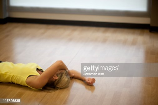 Woman lies exhausted on the gym floor. : Stock Photo