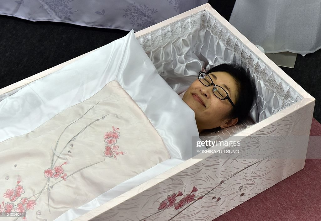 A woman lies in a coffin at the annual 'Shukatsu Festa 2014' funeral business fair in Tokyo on August 24 2014 Some 50 funeral and aging business...