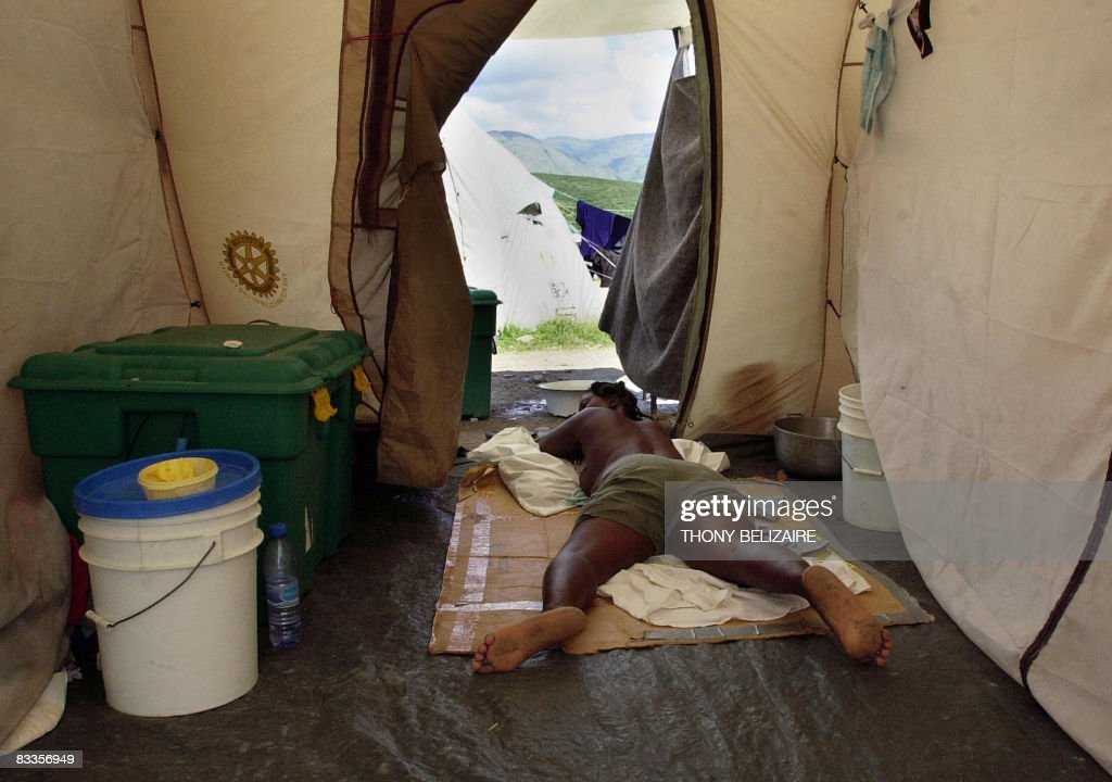 A woman lies in a tent in a makeshift camp on October 17, 2008 in the village of Cabaret, 35km north of Port-au-Prince, where some 700 people, mostly women and girls, have taken refuge after their homes were destroyed by hurricane Ike in September. AFP PHOTO/Thony BELIZAIRE