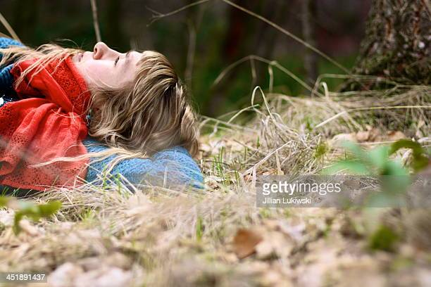Woman lies in bed ofgrass