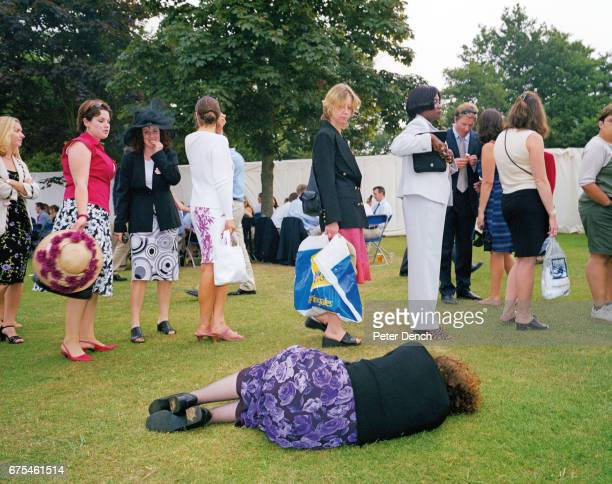 A woman lies on the grass next to the queue for the ladies' toilet at the Henley Royal Regatta July 2001