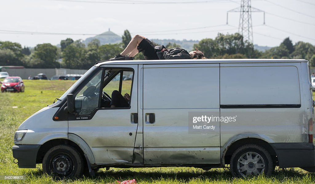 A woman lies on the roof of a van that is queuing in traffic as festival goers leave the Glastonbury Festival 2016 at Worthy Farm, Pilton on June 26, 2016 near Glastonbury, England. The Festival, which Michael Eavis started in 1970 when several hundred hippies paid just £1, now attracts more than 175,000 people.