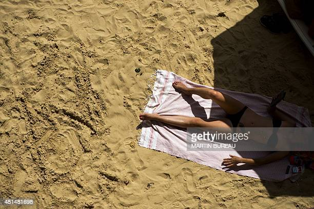 A woman lies on the sand of a temporary artificial beach set up on the banks of the river Seine as part of the 14th edition of Paris Plages on July...