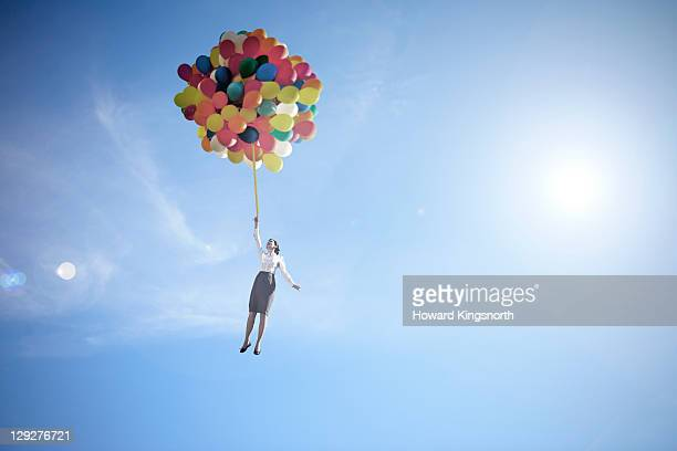 woman lifted into sky by huge bunch of balloons