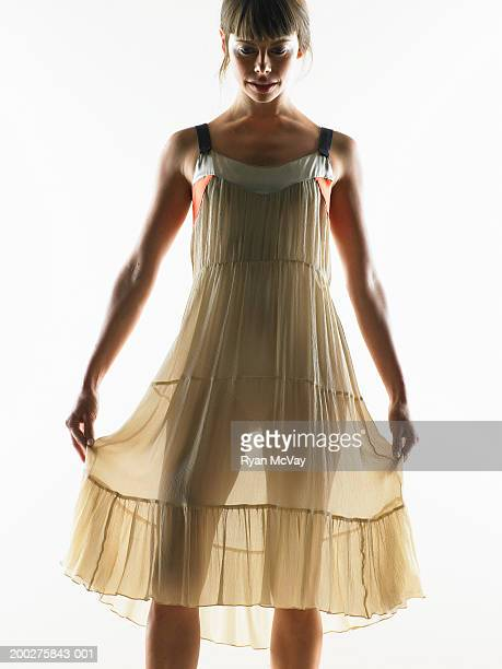 Donna sollevamento abito da entrambi i lati, guardare in basso