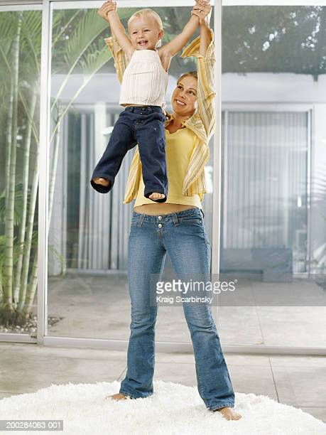 Woman lifting female toddler (21-24 months) above head, smiling