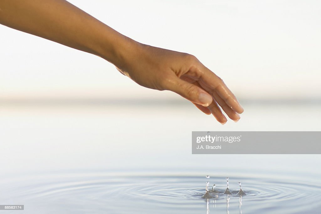 Woman lifting hand from pool of water : Stock Photo