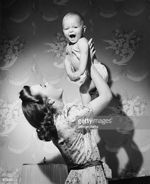 Woman lifting up baby (6-9 months) at home, (B&W)