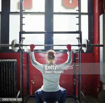 Woman lifting weights in gym, rear view : Stock Photo