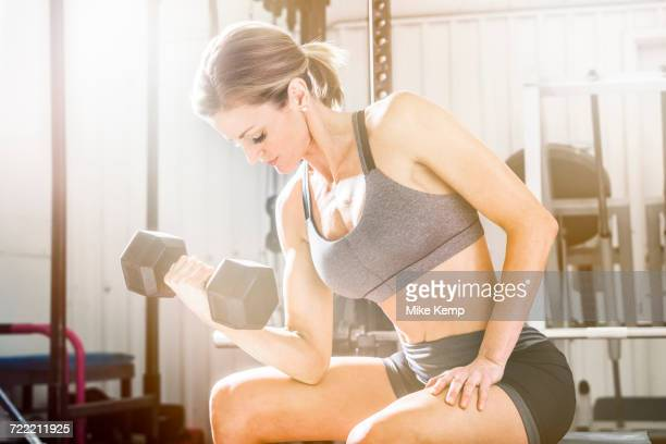 Woman lifting weights in gymnasium