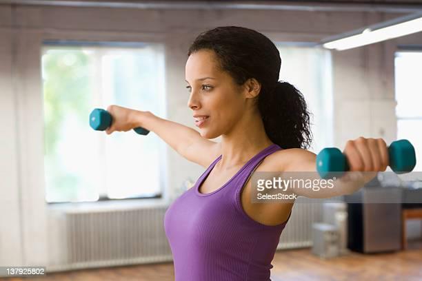 Frau heben Sie Gewichte im Fitness Center