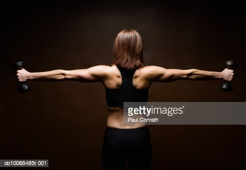 Woman lifting weights, rear view