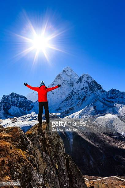 Woman lifts her arms in victory, Himalayas