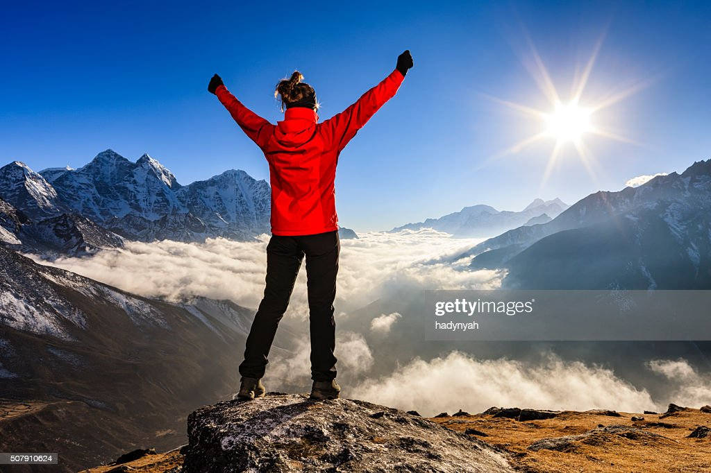 Woman lifts her arms in victory, Mount Everest National Park : Stock Photo