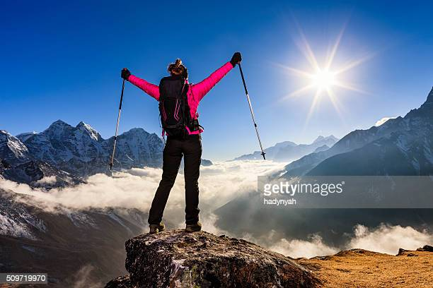 Woman lifts her arms in victory, Mount Everest National Park