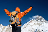 Woman lifts her arms in victory, Mount Everest on background