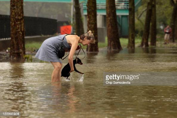 A woman lifts her dog up after flood waters became too deep for it to continue walking along the East River Bikeway after Hurricane Irene dumped more...