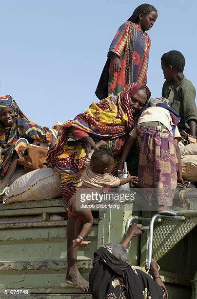 A woman lifts her infant child to join her other children in the back of an open truck headed for Libya on September 25 2004 in Agadez Niger...