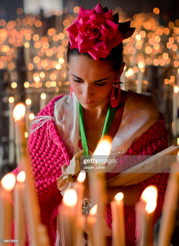 A woman lighs a candle inside the shrine of El Rocio on May 19, 2013 in El Rocio, Spain. The Romeria del Rocio procession brings together roughly a million pilgrims each year making their way for as long as seven days from throughout Andalusia by foot, on horsebacks and horse drawn carriages, to the doors of the Hermitage of El Rocio. On Sunday night, after reciting the Holy Rosary at candlelight, and the passing of all the simpecados in front of the chapel, with the one from the brotherhood of Matriz de Almonte as the last one, el salto de la reja begins, the jumping of the fence surrounding the Hermitage after which the Virgin of El Rocio is carried out onto the sandy streets of the small town for the 'Blanca Paloma' procession. Then, the long camino home begins. Dating back from 1653, it was in 1758, when the Virgin of Las Rocinas became known as the Virgin of El Rocio, that the pilgrimage started to take place in the weekend of the Sunday of Pentecost, 50 days after Easter Sunday.