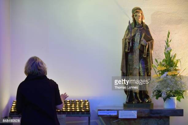 A woman light up a candle after the annual procession during the Catholic Hildegard Pilgrimage events in the Pilgrimage Church on September 17 2017...