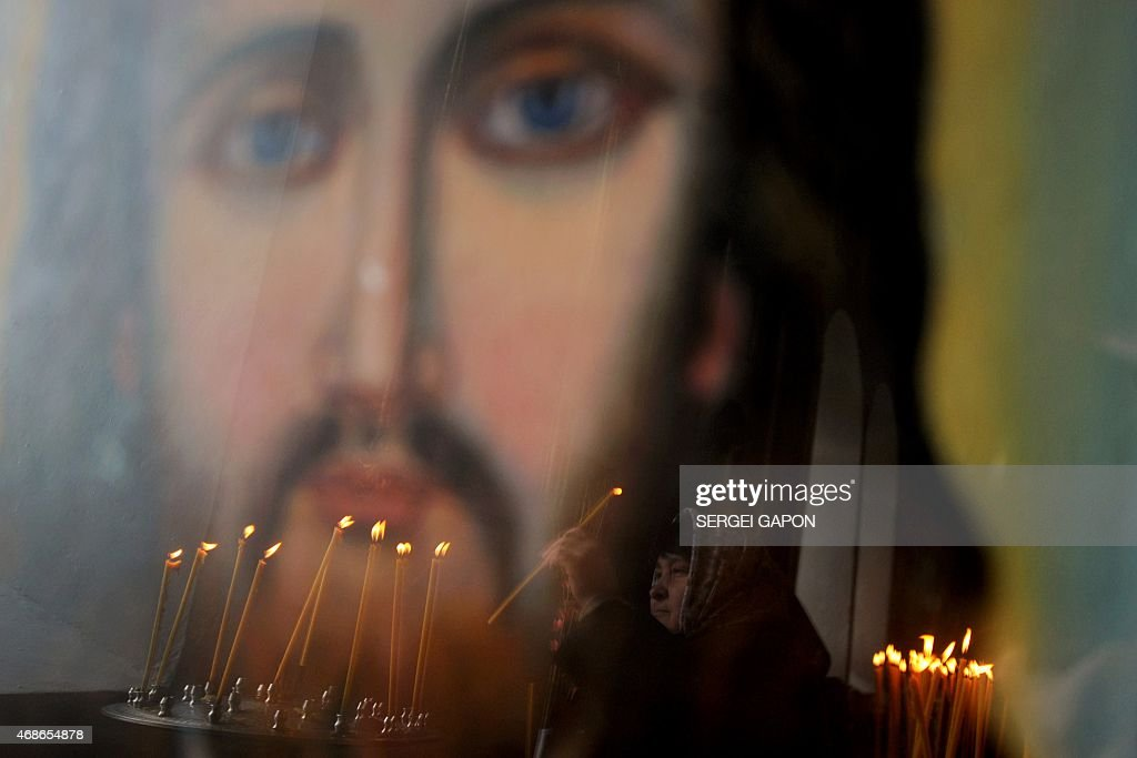 A woman lighting a candle is reflected in a painting of Jesus Christ during Easter Palm Sunday celebrations at a church in the village of Krevo some...
