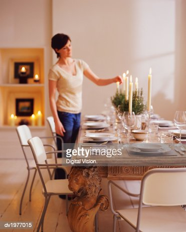 Woman Lighting Candles On A Dining Table In Preparation For Dinner Party Stock Photo