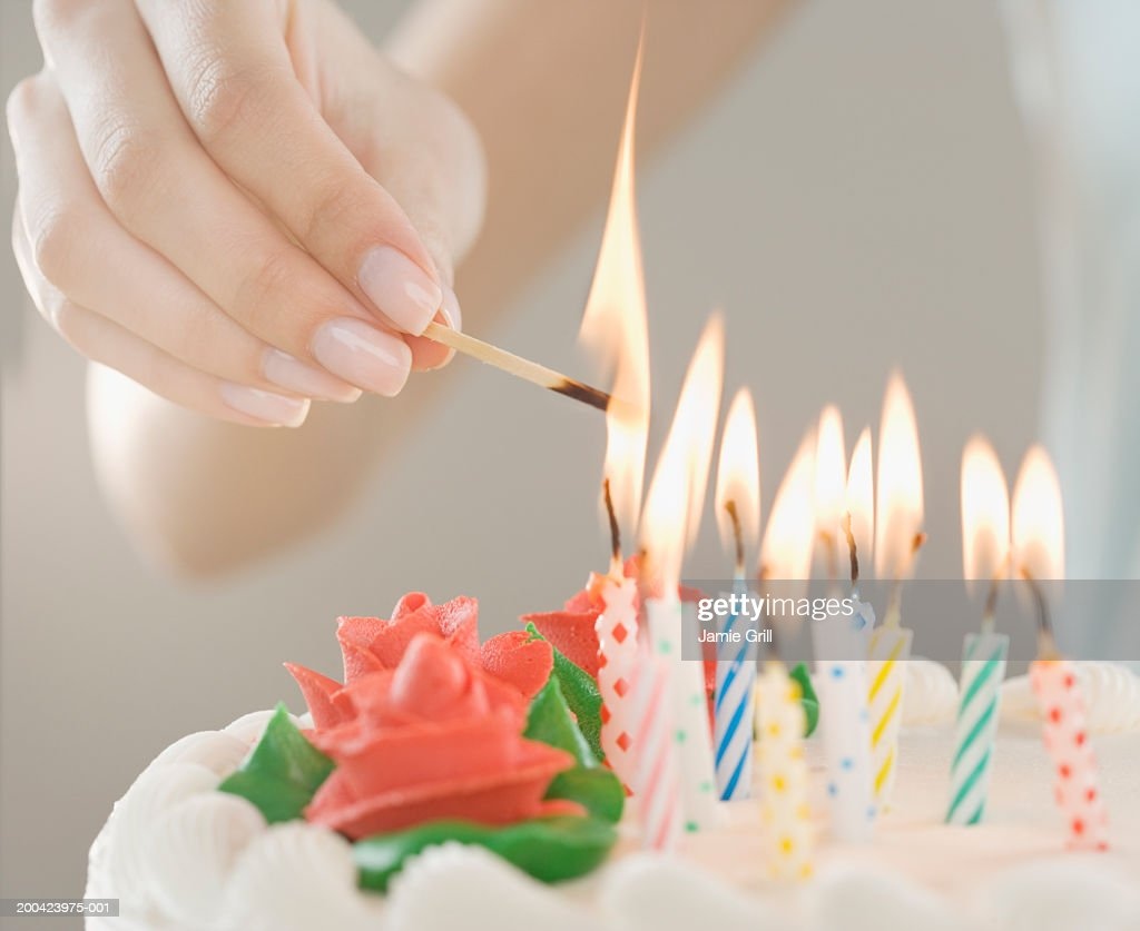 Woman lighting candles on cake, close-up : Stock Photo