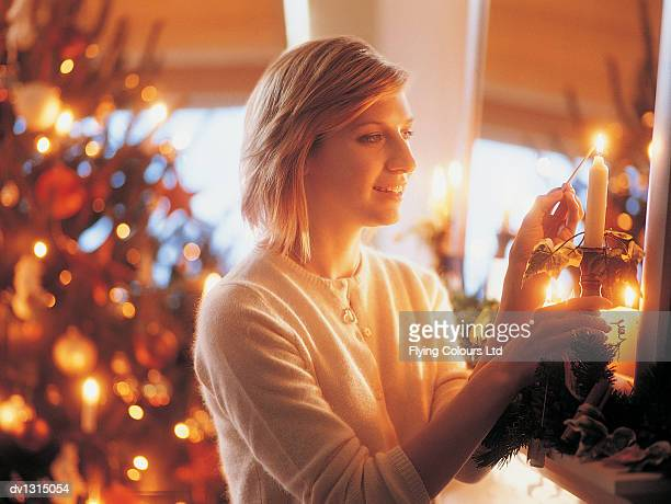 Woman Lighting Christmas Candles in Her Living Room