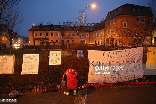 A woman lights a candle among banners left by people opposed to the attack next to the burntout remains of a former hotel that was to soon serve as a...