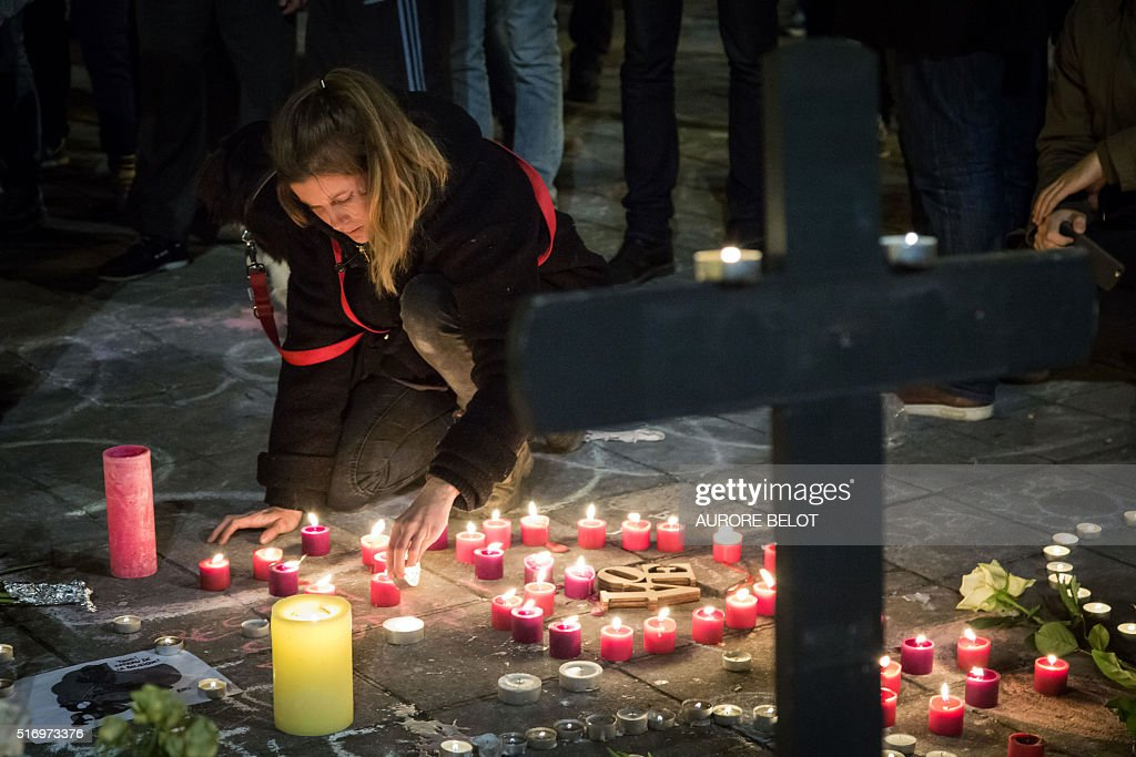 A woman lights a candle among floral tributes a cross and notes in front of the Bourse of Brussels on March 22 2016 in tribute to the victims of...