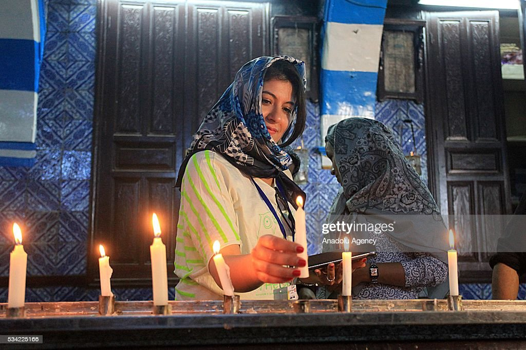 A woman lights a candle as Jews from different countries visit Synagogue La ghriba to celebrate Lag BaOmer in Djerba, Tunisia on May 25, 2016.