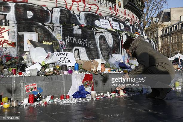 A woman lights a candle at a makeshift memorial at the place de la Republique in Paris on November 15 after a series of gun attacks occurred across...