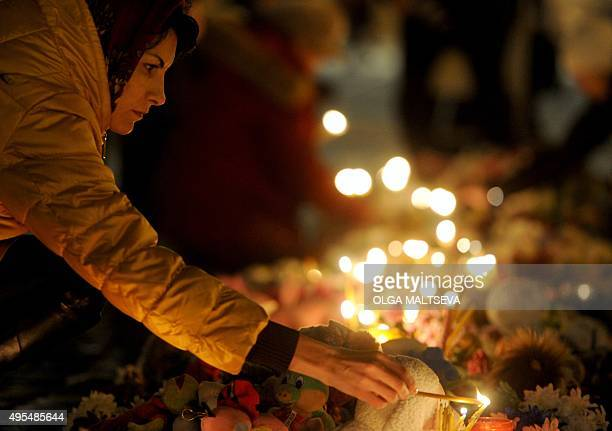 A woman lights a candle at a makeshift memorial for the victims of a jetliner crash on Dvortsovaya square in St Petersburg on November 3 2015 Russian...