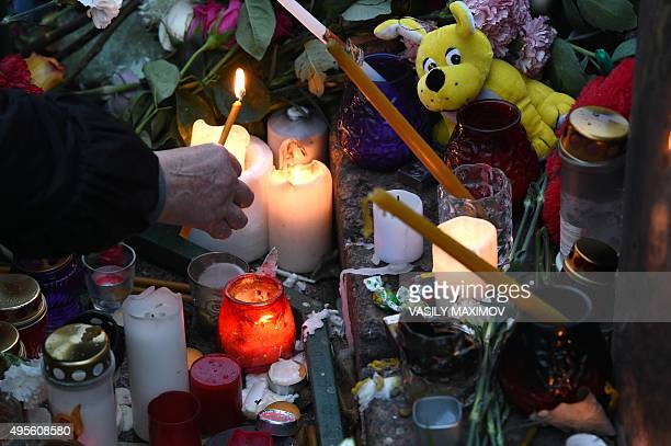 A woman lights a candle at a makeshift memorial for the victims of the Russian MetroJet Airbus A321 crash on November 4 2015 in Saint Petersburg...