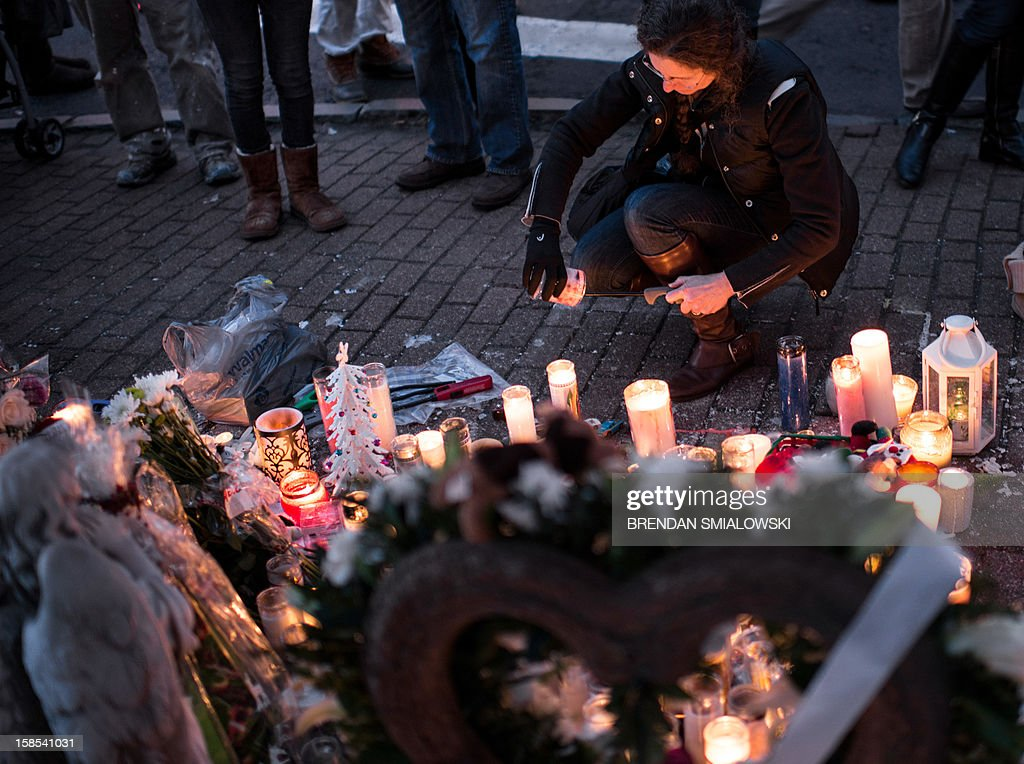 A woman lights a candle at a makeshift memorial on December 18, 2012 in Newtown, Connecticut. Students in Newtown, excluding Sandy Hook Elementary School, returned to school for the first time since last Friday's shooting at Sandy Hook which took the live of 20 students and 6 adults. AFP PHOTO/Brendan SMIALOWSKI