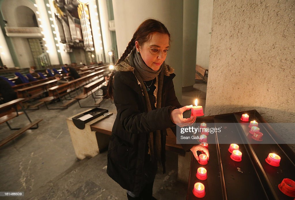 A woman lights a candle at St. Hedwig Catholic cathedral prior to a special evening mass following the announced resignation of Pope Benedict XVI on February 11, 2013 in Berlin, Germany. Pope Benedict XVI, born Josef Ratzinger in Germany, announced to Vatican clergy on Monday that he feels too physically frail to continue meeting the demands of being the Pope and will step down officially on February 28.