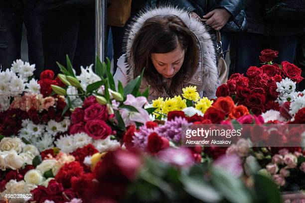 A woman lights a candle at the memorial of the victims of Airbus A321 crash at Pulkovo Airport on November 1 2015 in St Petersburg Russia A Russian...