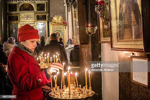 A woman lights a candle during a requiem in memory of the victims of the plane crash in Kazan Cathedral on November 1 2015 in St Petersburg Russia...