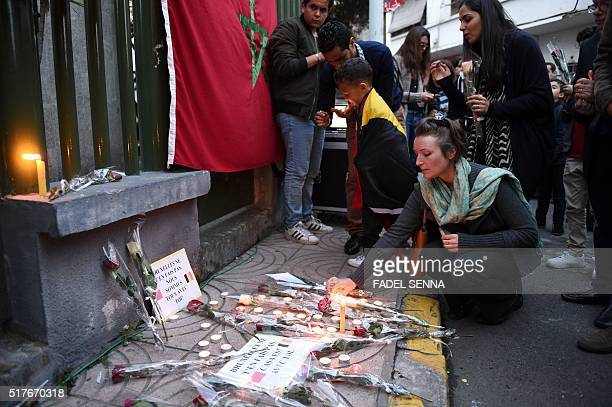 A woman lights a candle during a tribute to the victims of the Brussels attacks in Casablanca on March 26 four days after a triple bomb attack which...