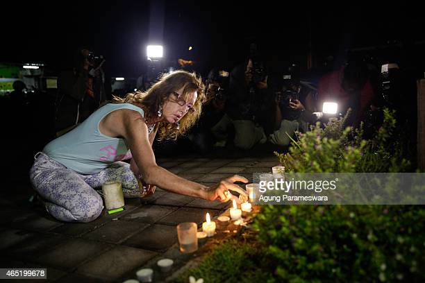 A woman lights a candle for Bali Nine duo Andrew Chan and Myuran Sukumaran before Indonesian police Indonesian transfered Bali Nine Duo Andrew Chan...