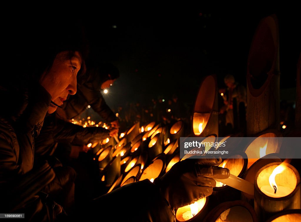 A woman lights a candle for victims of the 1995 'Great Hanshin earthquake' during a memorial ceremony on January 17, 2013 in Kobe, Japan. Memorial services were held to mark the 18th anniversary of the 1995 massive earthquake, hundreds of people gathered early this morning to pay their respects and light bamboo lanterns in the park for more than 6,400 people who lost their lives in the 7.3 magnitude earthquake.