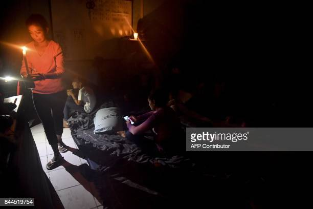 A woman lights a candle in a temporary shelter at a primary school during heavy rain caused by Hurricane Karina in Tecolutla Veracruz state Mexico on...