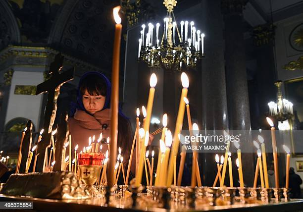 A woman lights a candle in Kazansky Cathedral in StPetersburg on November 2 in memory of the victims of a jetliner crash Russian airline...