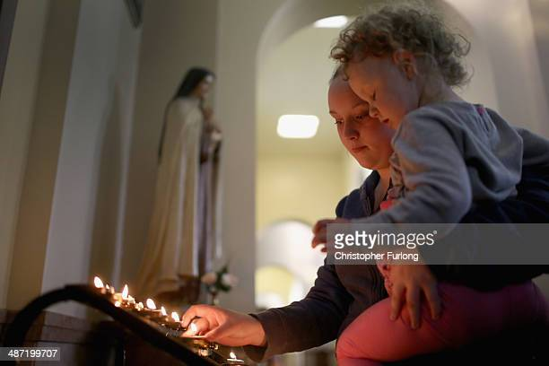 A woman lights a candle in memory of Anne Maguire in Corpus Christi Catholic Church which is adjacent to Corpus Christi Catholic College in Neville...