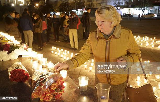 A woman lights a candle in Simferopol on November 1 2015 in memory of the victims of a jetliner crash Russia mourned its biggest ever air disaster...