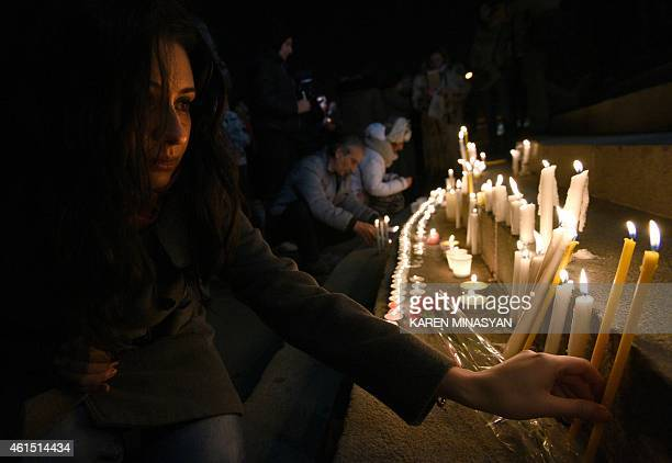 A woman lights a candle in the center of Yerevan on late January 13 2015 in tribute to the six members of the same family allegedly killed by Russian...