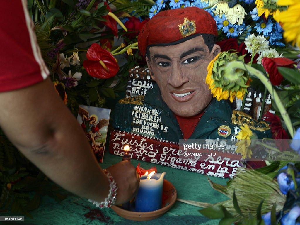 A woman lights a candle inside the newly inaugurated Santo Hugo Chavez del 23 chapel, at the 23 de Enero neighbourhood, in the surroundings of the museum where the remains of President Chavez lay, in Caracas on March 27, 2013. AFP PHOTO